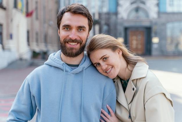 Donna di smiley in posa mentre appoggiato a un uomo all'aperto