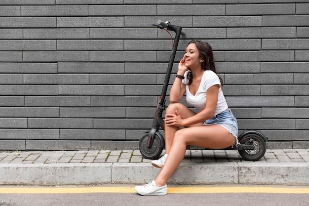 Donna di smiley in posa mentre è seduto su uno scooter elettrico