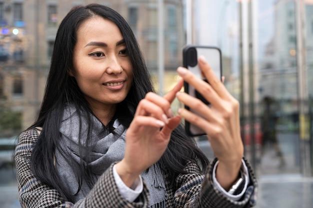 Donna sorridente che cattura selfie in città