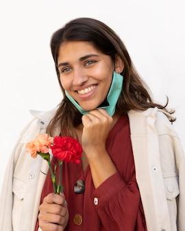Donna sorridente con maschera facciale e fiori