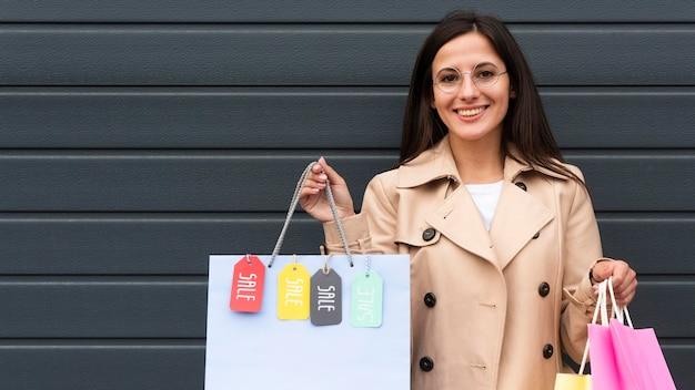 Donna sorridente con gli occhiali che tengono i sacchetti della spesa con i tag di vendita