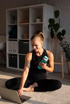 Donna sorridente con laptop e bottiglia d'acqua