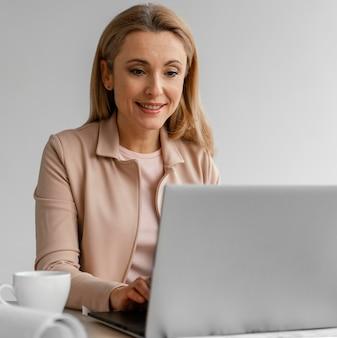 Donna sorridente che lavora nel suo ufficio