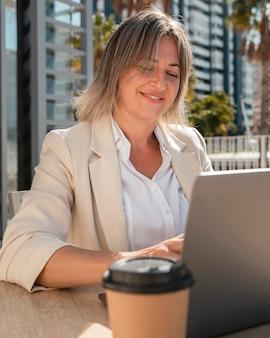 Donna sorridente che lavora al tavolo