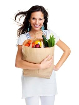 Giovane donna sorridente che tiene il sacchetto di carta con generi alimentari su priorità bassa bianca