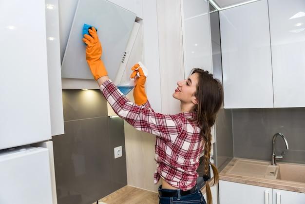 Sorridente ragazza adulta pulizia cucina con flacone spray e un panno in microfibra