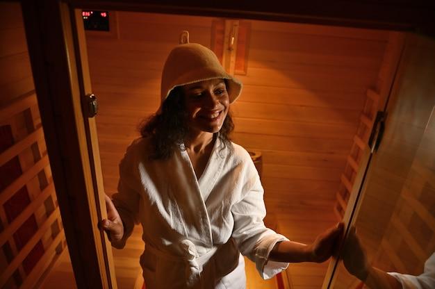 Donna sorridente di etnia afroamericana nella sauna di legno a infrarossi. trattamento spa. cura del corpo e della pelle