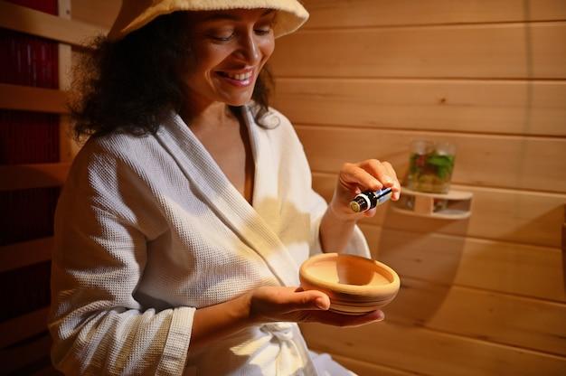 Donna sorridente di etnia afroamericana che versa poche gocce di olio essenziale di basilico in un mortaio di legno mentre si rilassa nella sauna di legno wooden