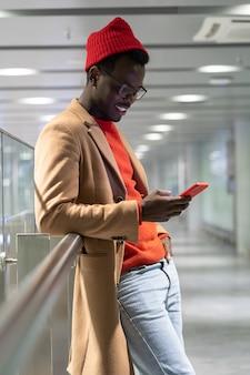 Sorridente uomo millenario hipster afroamericano indossa cappotto beige e cappello rosso utilizzando il cellulare, in chat nei social network, digitando un messaggio. verticale.