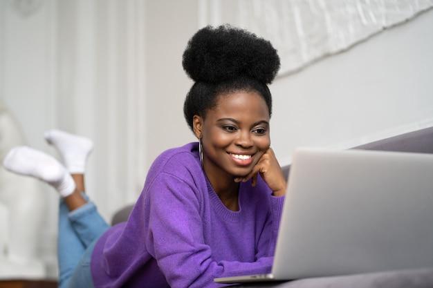 La donna millenaria afroamericana sorridente con l'acconciatura afro indossa un maglione viola sdraiato sul divano, a riposo, guardando la webcam della fotocamera e parlando in una videochiamata o skype con gli amici, guardando un film.