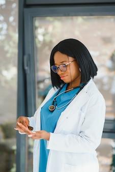 Infermiera afroamericana sorridente con la pillola della holding dello stetoscopio