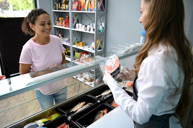Sorridente donna afroamericana, cliente al negozio di frutti di mare che acquista pesce. il pescivendolo serve filetto di salmone rosso fresco. vendita al dettaglio di frutti di mare.