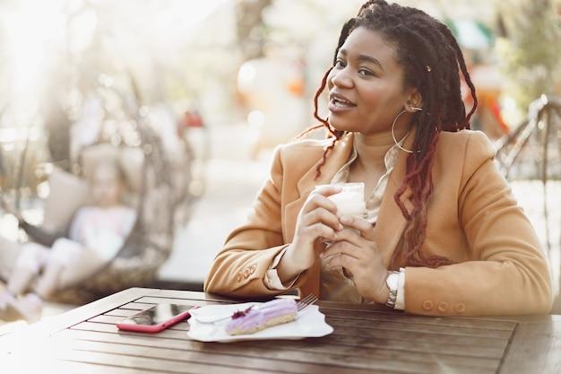 Sorridente donna afroamericana che beve caffè e mangia dessert in un caffè all'aperto