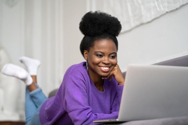 La donna afroamericana sorridente con l'acconciatura afro indossa un maglione viola sdraiato sul divano, a riposo, guardando la webcam
