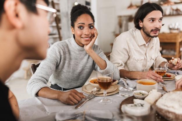 Sorridente donna afroamericana con capelli ricci scuri seduto al tavolo appoggiato sulla mano pensieroso