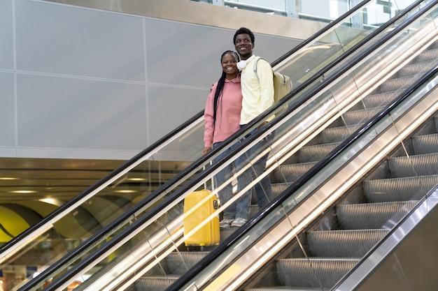 Sorridente coppia africana in aeroporto in piedi su una scala mobile con la valigia che viaggia dopo la fine del blocco covid