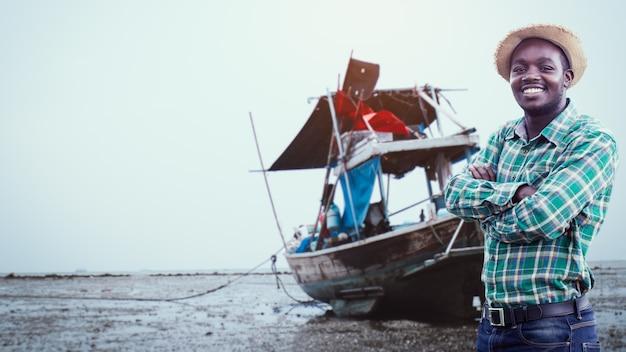 Un sorridente pescatore africano in piedi accanto alla sua barca da pesca