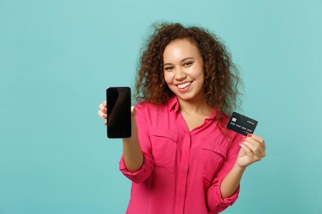 La ragazza africana sorridente in abbigliamento casual tiene il telefono cellulare con lo schermo vuoto in bianco, carta di credito della banca isolata su fondo blu del turchese. concetto di stile di vita di emozioni sincere della gente. mock up copia spazio.