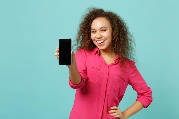 La ragazza africana sorridente in vestiti casuali tiene il telefono cellulare con lo schermo vuoto in bianco isolato sul fondo blu della parete del turchese in studio. persone sincere emozioni, concetto di stile di vita. mock up copia spazio.