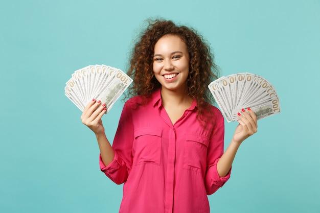 Sorridente ragazza africana in abiti casual con ventaglio di soldi in banconote in dollari, denaro contante isolato su sfondo blu turchese parete. persone sincere emozioni, concetto di stile di vita. mock up copia spazio.