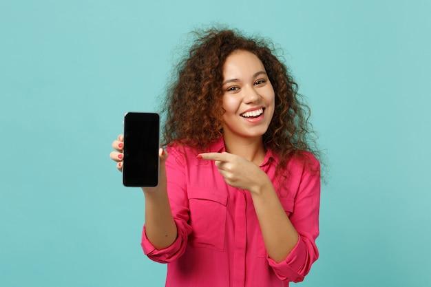 Sorridente ragazza africana in abiti casual punta il dito indice sul telefono cellulare con schermo vuoto vuoto isolato su sfondo blu turchese. persone sincere emozioni, concetto di stile di vita. mock up copia spazio.