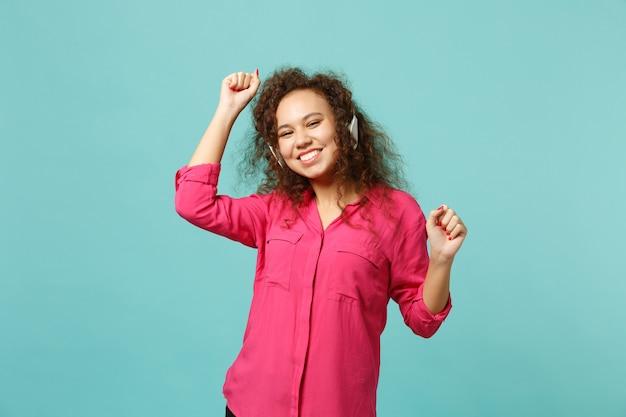 Sorridente ragazza africana in abiti casual rosa ascoltando musica con le cuffie e ballando isolato su sfondo blu muro turchese. persone sincere emozioni, concetto di stile di vita. mock up copia spazio.