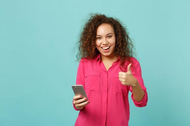 Sorridente ragazza africana in abiti casual rosa che mostra pollice in su utilizzando il telefono cellulare digitando un messaggio sms isolato su sfondo blu turchese. concetto di stile di vita di emozioni sincere della gente. mock up copia spazio.