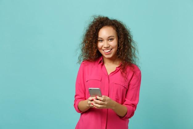 Sorridente ragazza africana in abiti casual rosa utilizzando il telefono cellulare, digitando un messaggio sms isolato su sfondo blu muro turchese in studio. persone sincere emozioni, concetto di stile di vita. mock up copia spazio.