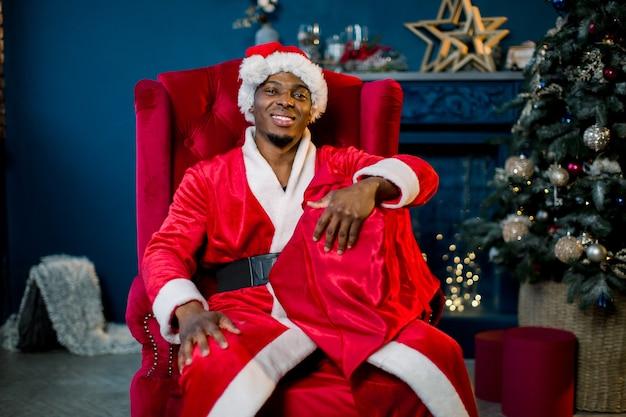 Babbo natale maschio africano sorridente che tiene un sacco rosso con i regali di natale mentre era seduto sulla sedia rossa