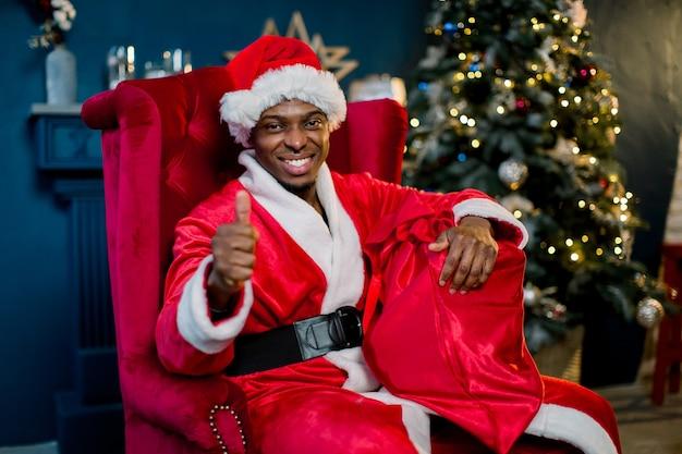 Babbo natale maschio africano sorridente che tiene un sacco rosso con i regali di natale