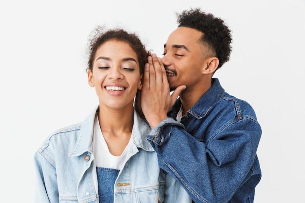 Uomo africano sorridente che parla qualcosa in orecchio della sua amica piacevole che ascolta con gli occhi chiusi sopra la parete grigia