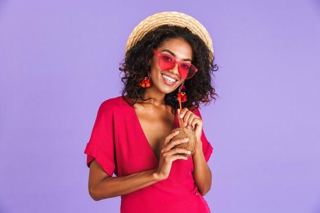 Sorridente donna africana in abito, cappello di paglia e occhiali da sole in posa con cocktail