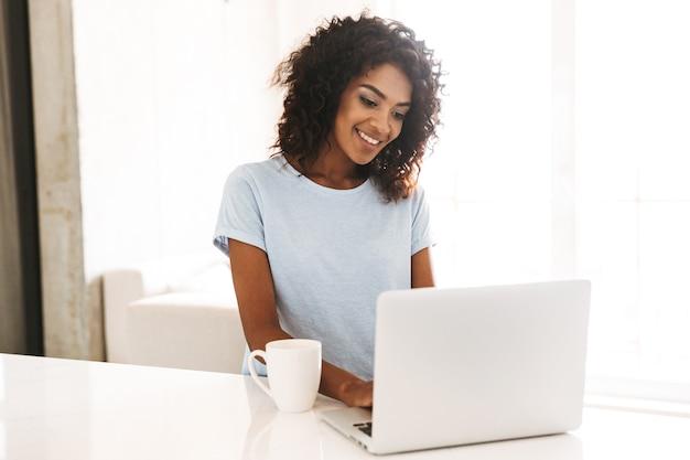 Sorridente donna africana utilizzando il computer portatile