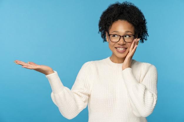 La donna africana sorridente indossa il ponticello bianco che tiene lo spazio della copia sul palmo per pubblicità, prodotto, vendita