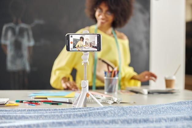 Sorridente insegnante afroamericano in elegante maglione giallo conduce lezioni di fashion design online in