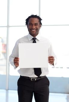 Uomo d'affari afroamericano sorridente che tiene una carta bianca