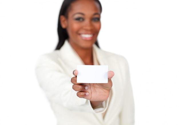 Donna di affari afroamericana sorridente che tiene una carta bianca