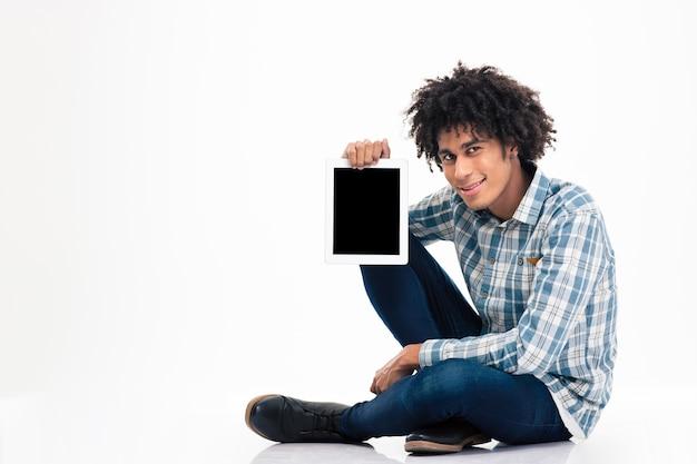Sorridente uomo afroamericano seduto sul pavimento e mostrando lo schermo del computer tablet vuoto isolato su un muro bianco