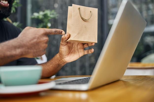 Un sorridente uomo afroamericano seduto al tavolo e indicando un piccolo sacchetto di carta in mano