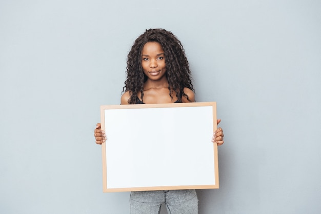 Sorridente donna afro che mostra bordo bianco su muro grigio