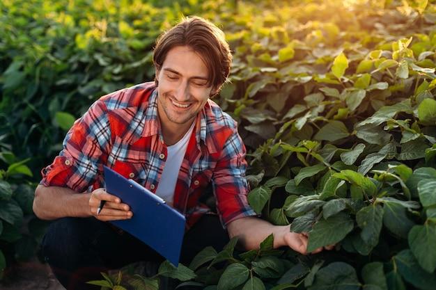 Sorridente agronomo segue la crescita dell'agricoltura, prende appunti