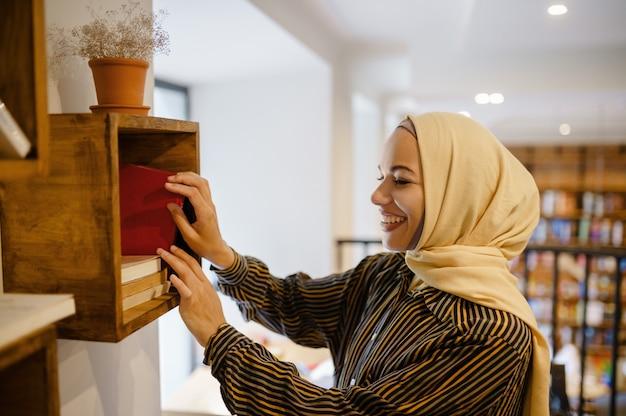 Sorridente ragazza araba in hijab presso lo scaffale per libri, interno del caffè universitario su priorità bassa. donna musulmana con libri seduti in biblioteca.