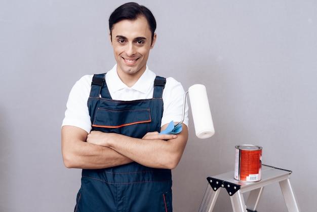 Maestro arabo sorridente con vernice e pennello in mano.