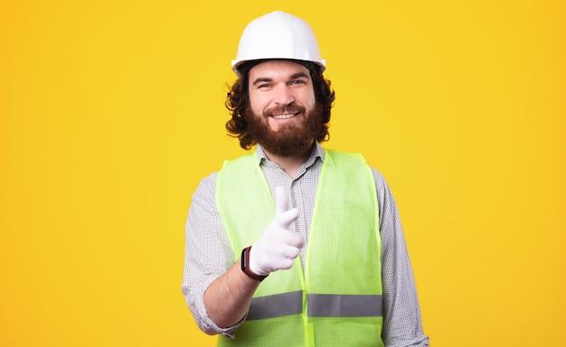 Sorridente architetto uomo in piedi su sfondo giallo e punta verso la telecamera