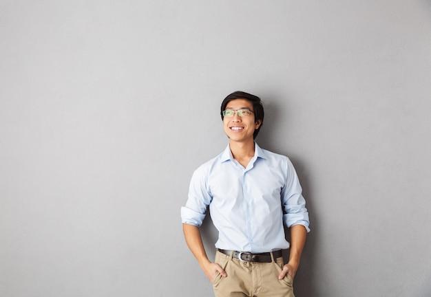 Sorridente uomo d'affari asiatico in piedi isolato, guardando lontano