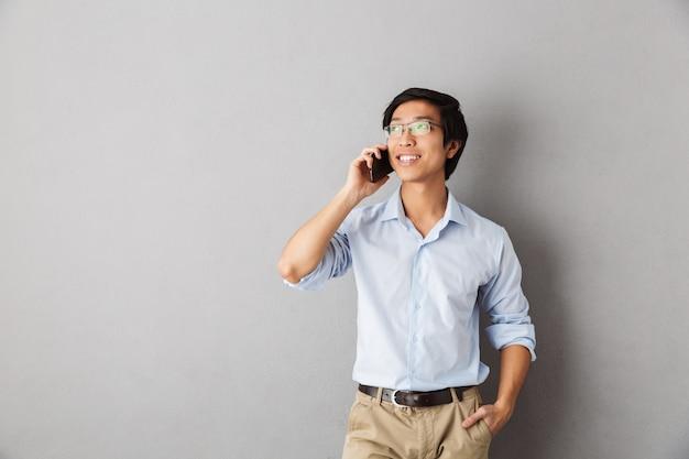 Sorridente uomo d'affari asiatico in piedi isolato, parlando al telefono cellulare