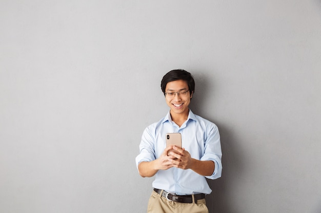 Sorridente uomo d'affari asiatico in piedi isolato, utilizzando il telefono cellulare