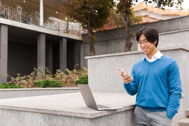 Uomo d'affari asiatico sorridente in piedi all'aperto con computer portatile e telefono cellulare