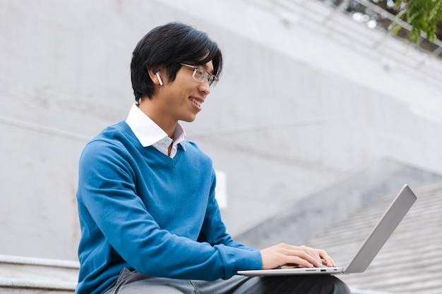 Sorridente uomo d'affari asiatico utilizzando il computer portatile all'aperto