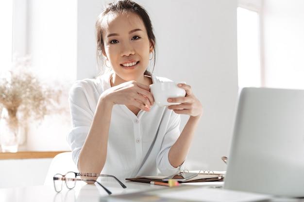Donna asiatica sorridente di affari che beve caffè e che esamina la parte anteriore mentre sedendosi dalla tavola in ufficio